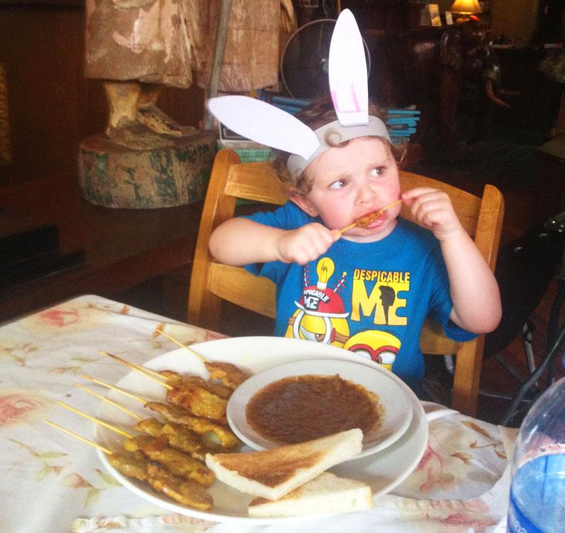 Reuben-Eating-Satay-Chicken,-Bangkok-with-kids