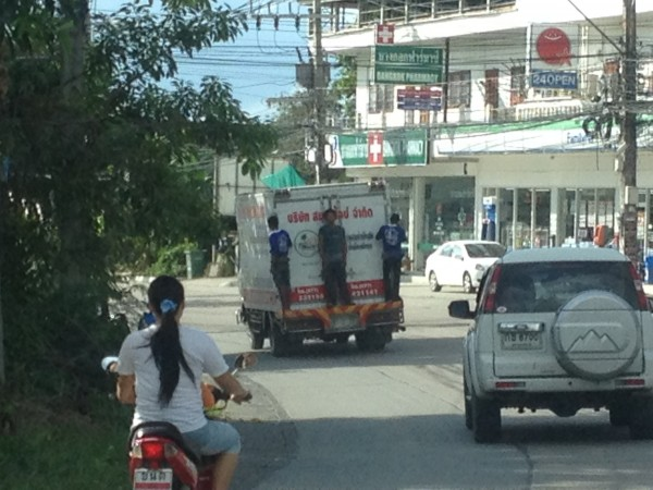 People hanging off the back of a delivery truck