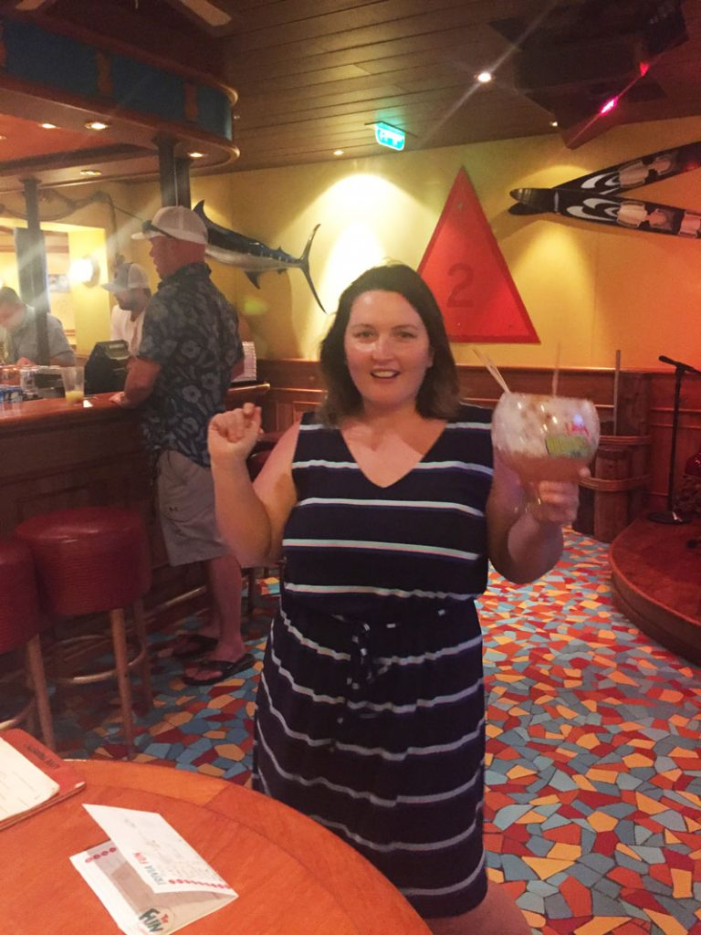 Bethaney dancing to the steel drums and drinking a fishbowl margarita at the Red Frog Pub on Carnival Breeze
