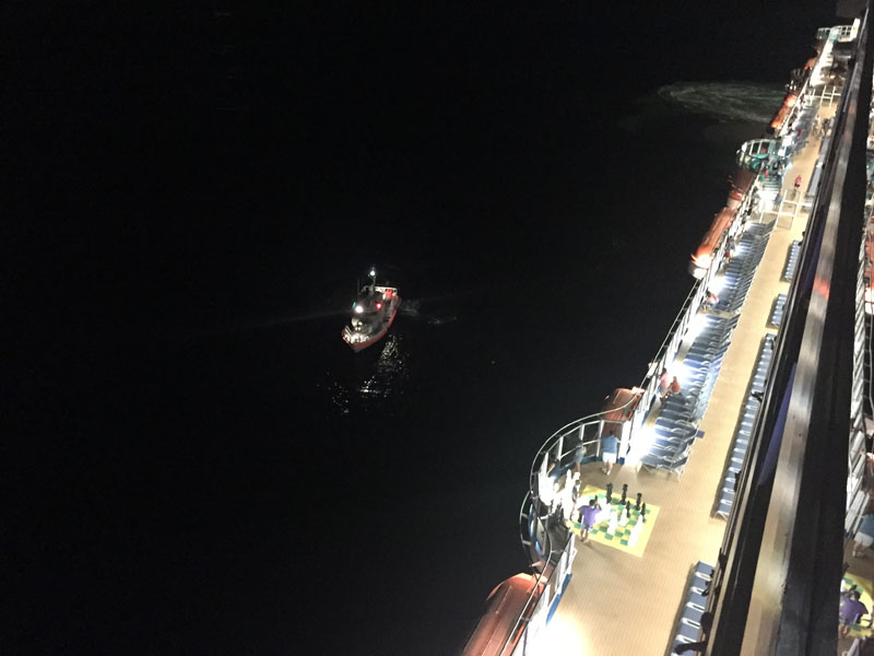 Coast Guard boat rescuing an ill passenger on the Carnival Breeze