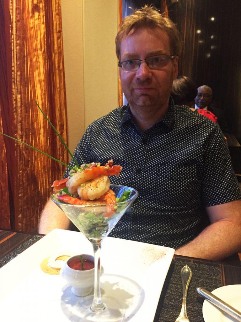 Lee enjoying a shrimp cocktail at Fahrenheit 555 Steakhouse on Carnival Breeze