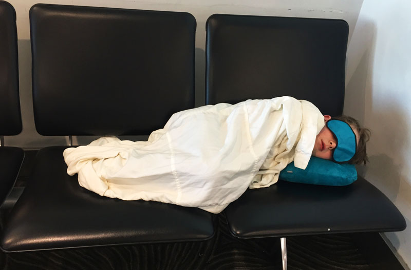 Reuben sleeping on an airport bench with eye mask and neck pillow after long flight from Auckland to Shanghai